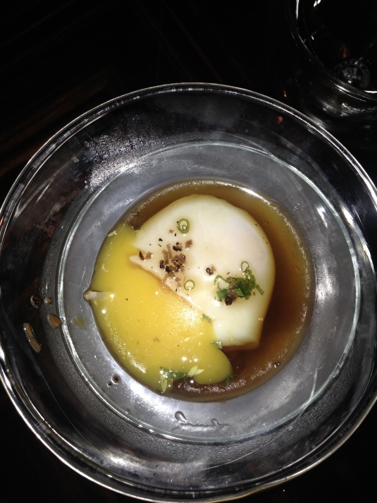 The cup holds a perfectly poached egg laying in a thick creamy broth...